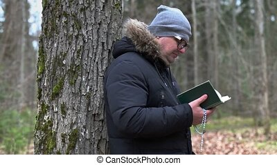 Man with rosary reading Bible and praying near tree