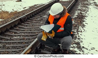 Railroad worker checking documentation near railway
