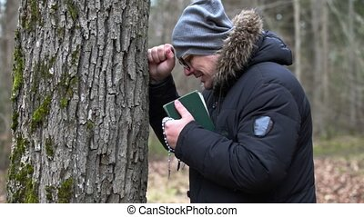 Sorrowful man with Bible and rosary crying near tree