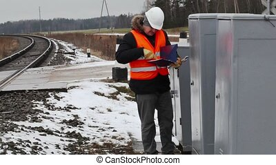 Railroad worker with documentation near electrical enclosure