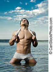 sexy man - the very muscular handsome sexy guy in water, on...