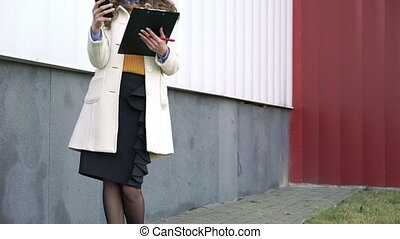 Portrait of happy woman standing outdoor using tablet and smartphone