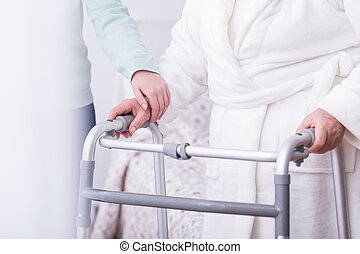 Person holding walking zimmer - Close up of disabled person...
