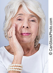 Woman and working anti-aging cream - Older spruce woman...
