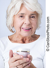 Anti-aging cream helps to keep your face young - Elderly...