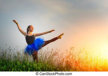 Toung beautiful ballerina dancing outdoors