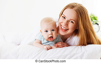 happy family mother  with baby in bed