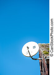 satelite dish - satelite is attached to the wall of the...