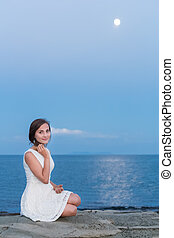 Portrait of pretty young girl at the beach with moon shining