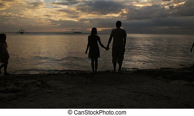 silhouette of family on the beach at sunset
