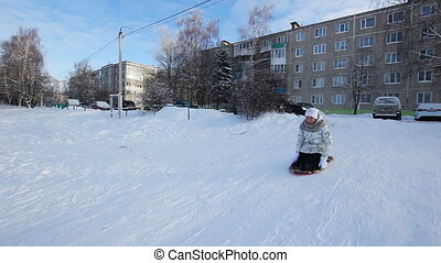 Yong girl sledging down hill - Girl sledging down hill,...