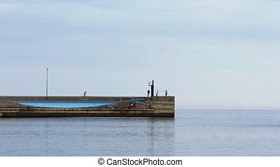 Fishermen on a concrete pier trying to catch fish Wall built...