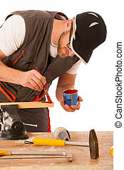 A carpenter pinting wood in red color isolated over white...
