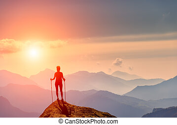 Woman at the top of a mountain looking horizon colored