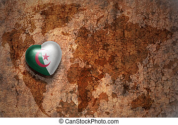 heart with national flag of algeria on a vintage world map crack paper background.