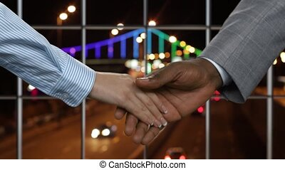 Young woman shakes businessmans hand Handshake on night road...