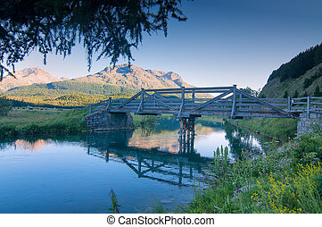 Wooden bridge on the mountain river in the summer