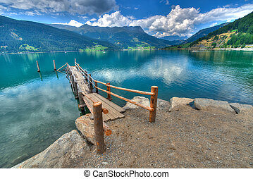 Wooden pier on the mountain lake in  South Tyrol Italy