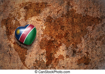 heart with national flag of namibia on a vintage world map...