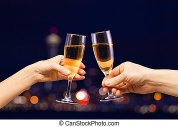 Man and woman hands with full champagne glasses