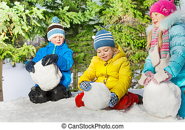 Kids roll snow balls in the park - Group of kids roll snow...