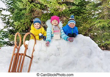 Kids boys and girl behind snow wall with snowballs