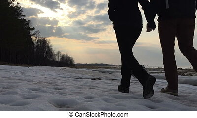 Young couple holding hands slowly walks. - Young couple...