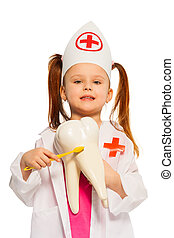 Little girl wearing whites brushing tooth model - Little...