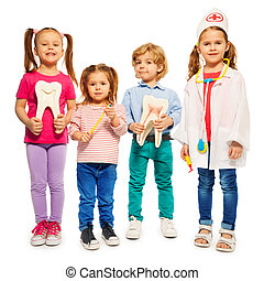 Four little children playing doctors with teeth dummies,...