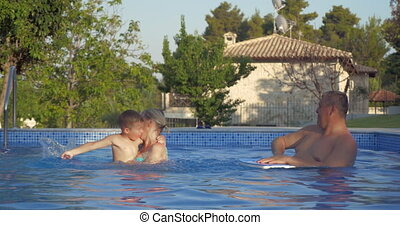 Grandparents and grandson having fun in the pool -...