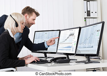 Businesspeople Analyzing Stock Charts On Multiple Computers
