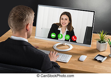 Businessman Video Conferencing On Computer - Young...
