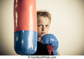 Frowning blond boy stands beside punching bag - Frowning...