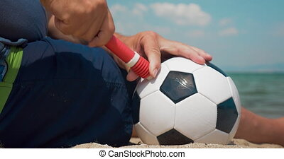 Man pumping a football on the shore - Close-up shot of a man...