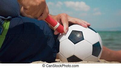 Man pumping a football on the shore - Close-up shot of a man...