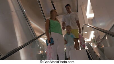Family riding down on escalator in shopping mall - Mother,...