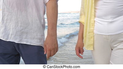 Senior couple holding hands during walk on beach