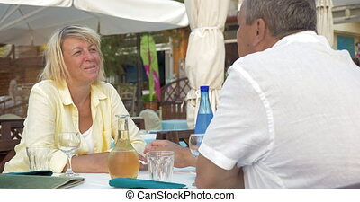 Man and woman sitting in restaurant, talking and laughing.
