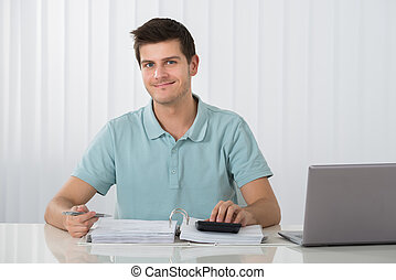 Man Calculating Tax - Photo Of Young Man Calculating Tax At...