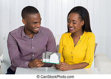 Young Couple Holding A House Model - Young Happy African...
