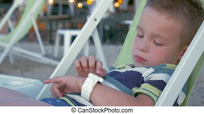 Modern gadgets for any age - Little boy in chaise-longue at...
