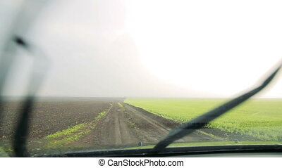 Rain on the  fields view through the windshield of the car