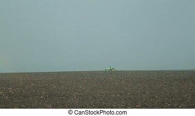 Raining. Modern tractor cultivating field's soil in full HD