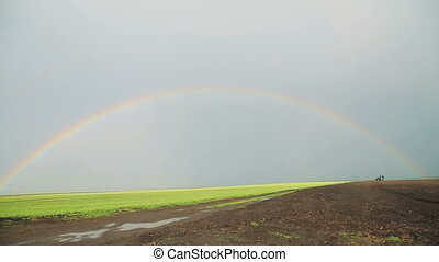 Rainbow over the fields and tractor in full HD