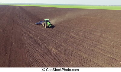 Aerial view of tractor cultivating fields soil in spring day...