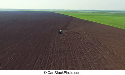 Aerial view of fields, tractor plowing the soil in spring...