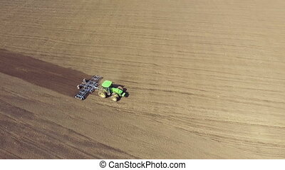 Aerial view of agriculture tractor cultivating fields soil...