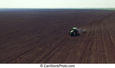 Aerial view of tractor cultivating fields soil in full HD