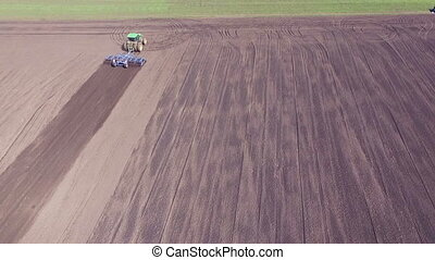 Aerial view of agriculture vehicle cultivating fields soil...