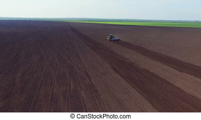 Aerial view of modern tractor plowing the soil in sunny day....